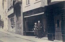 Minderbroedersstraat 5 - Het echtpaar P. Vanstraelen-Tempels voor hun winkel (privécollectie)