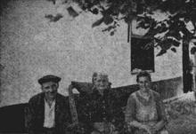 Stieneke Celus tussen haar zoon Jef en haar dochter, in de schaduw van een lindeboom, vóór hun proper huizeke (uit: Waar de Heksen hun Bezems huurden… / Zeven der laatste Bezembinders van Kiewit tellen samen 559 Jaar (1953), p. 1)
